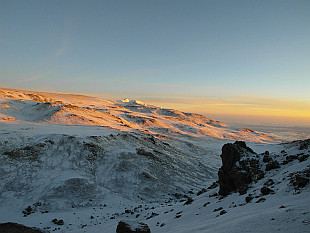 first sunrays hitting the summit plateau of Kibo